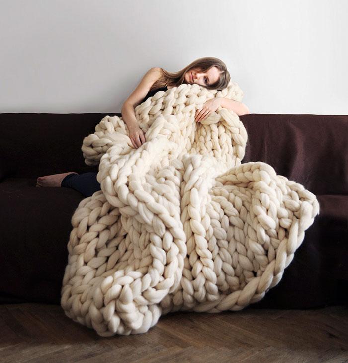 coperta in filato gigante bianca e ragazza sul divano