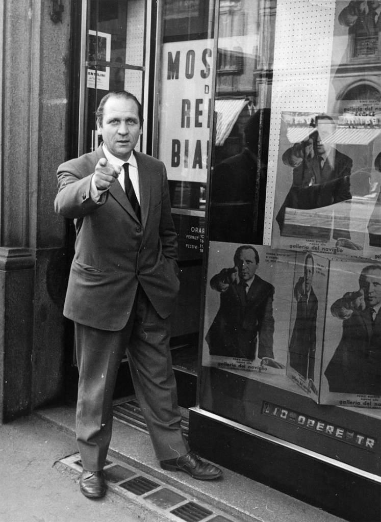 foto bianco e nero uomo in giacca e cravatta davanti vetrina punta dito verso spettatore