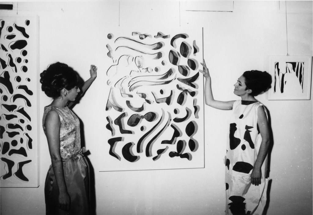 foto bianco e nero opera d'arte moderna astratta e due ragazze a destra e sinistra