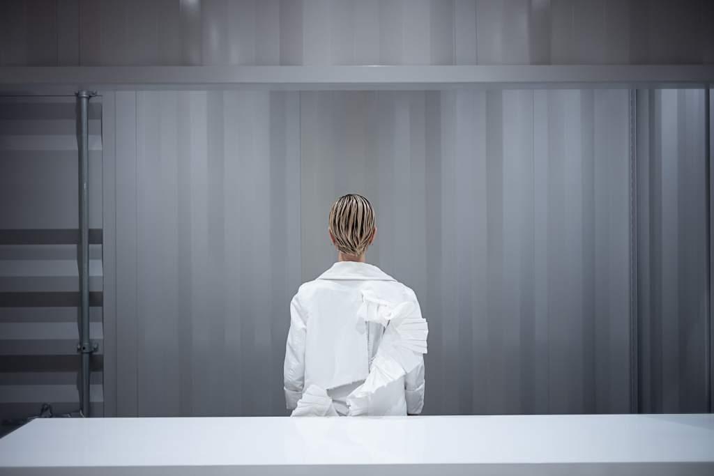 opera d'arte fotografia colori interno con figura umana di spalle con camice bianco sfondo grigio
