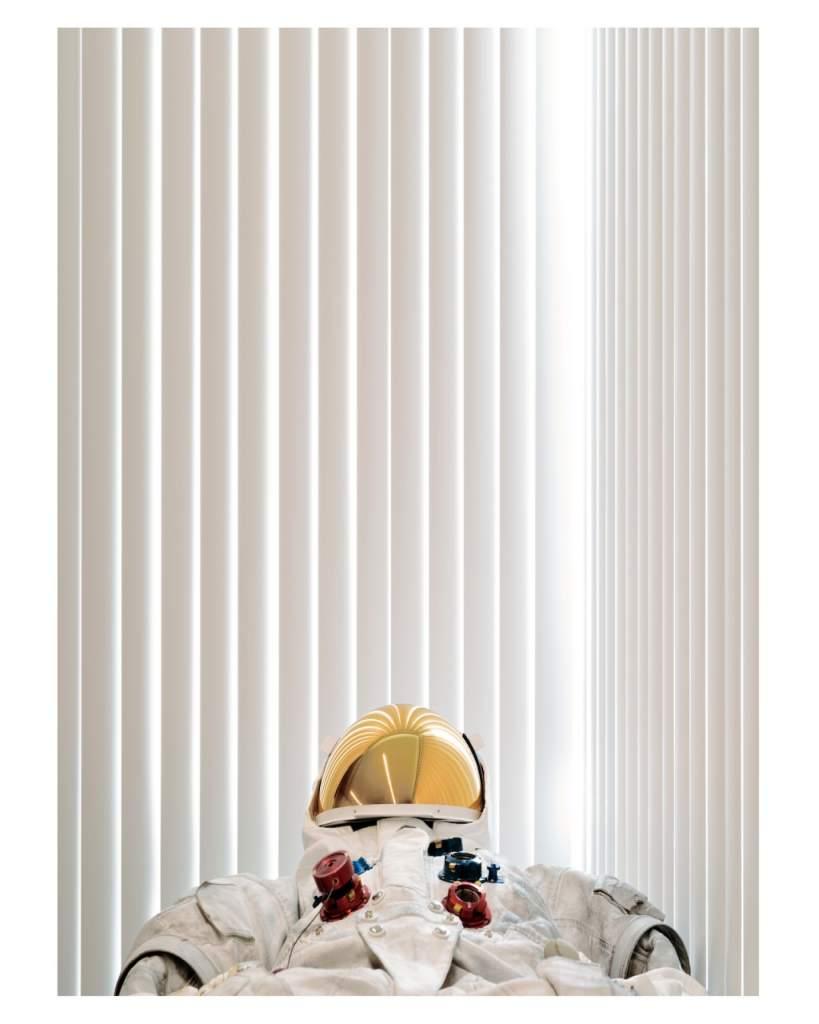 opera d'arte fotografia colori, tuta astronauta bianca sdraiaita, visiera casco oro, sfondo bianco
