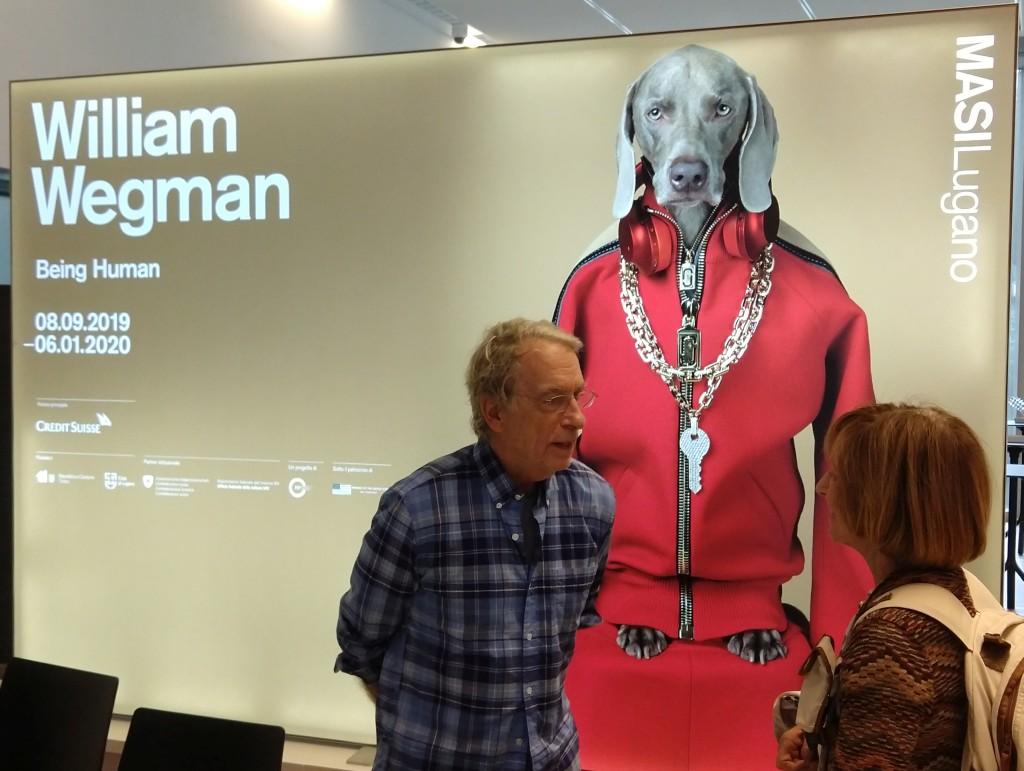 foto, interno, colori, artista americano William Wegman uomo occhiali capelli bianchi, intervistato da giornalista donna