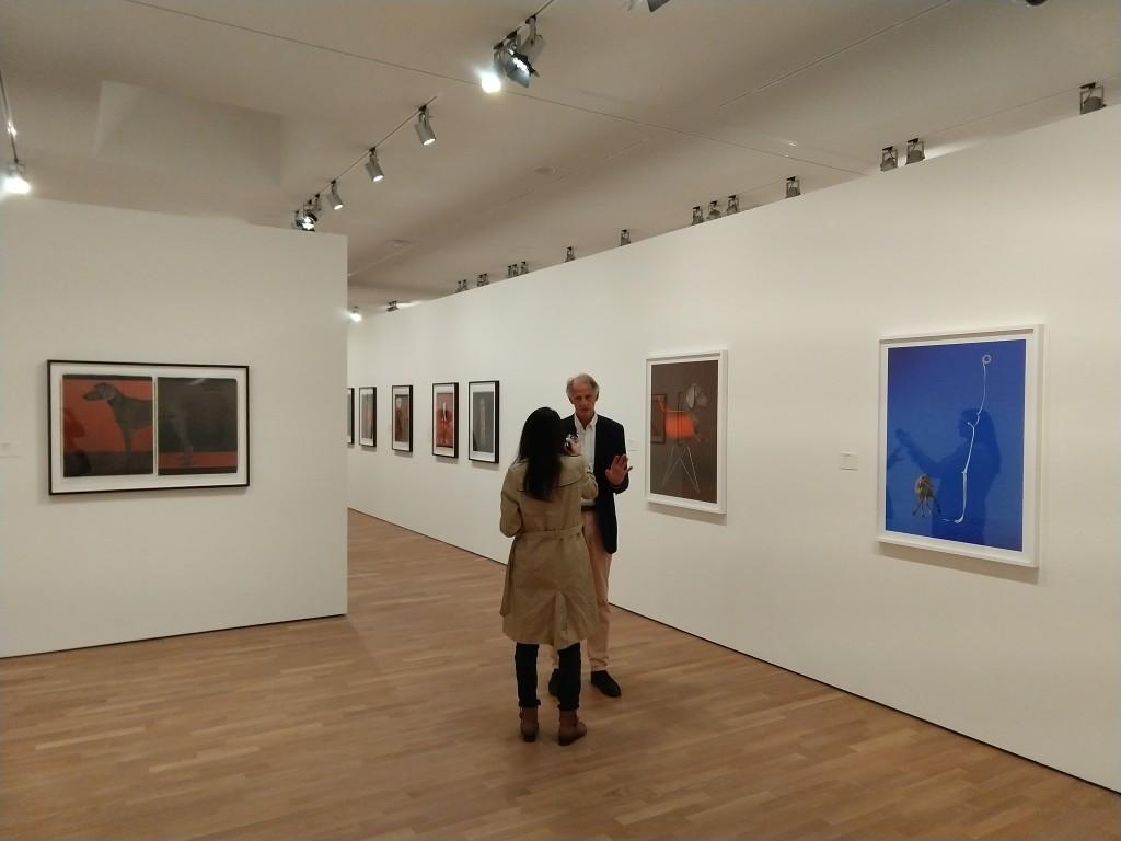 foto, interno, colori, curatore americano William Wegman uomo capelli bianchi, intervistato da giornalista donna, sfondo mostra fotografica