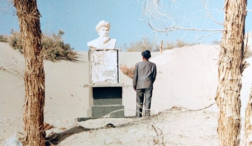 fotografia, colori, esterno, deserto peino sole, uomo di spalle con cappello osserva dal basso statua bianca di uomo con cappello