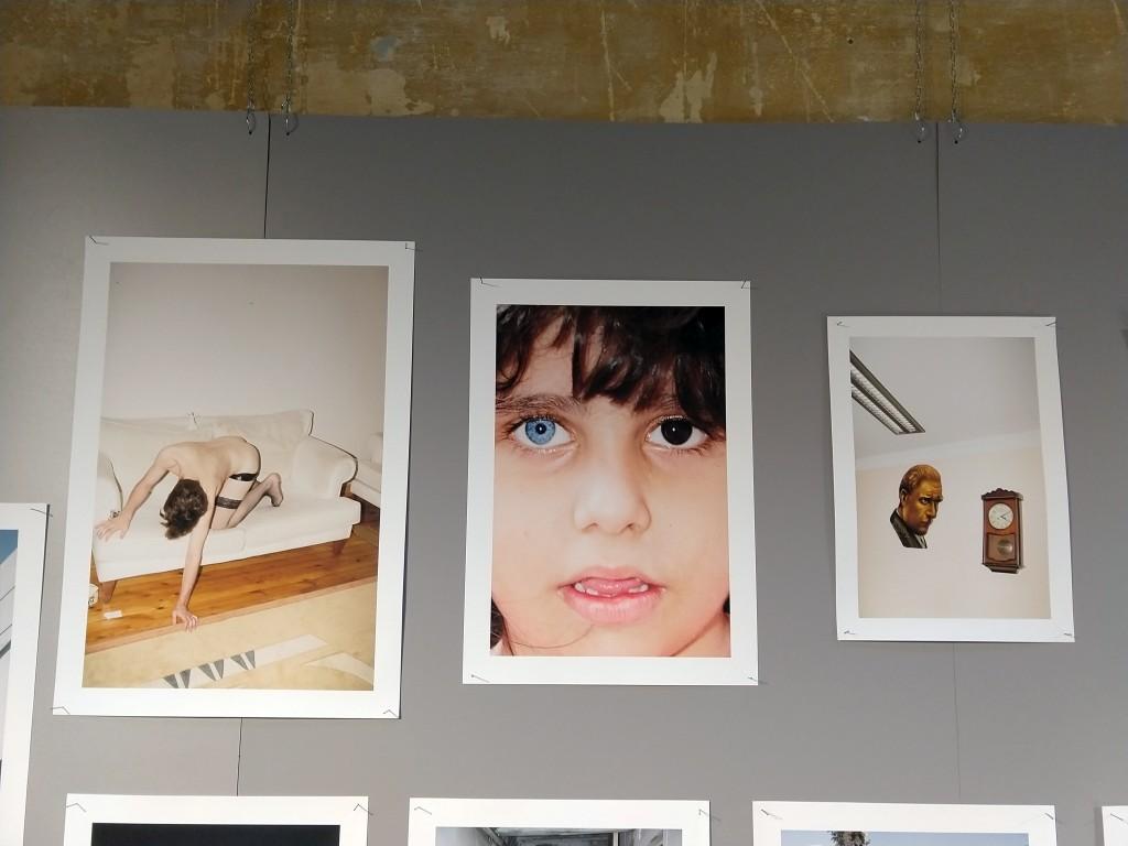 3 fotografie a colori, a sinistra uomo nudo su un divano bianco, al centro primo piano bimba con un occhio castano e uno azzurro, a destra interno con pendola a muro