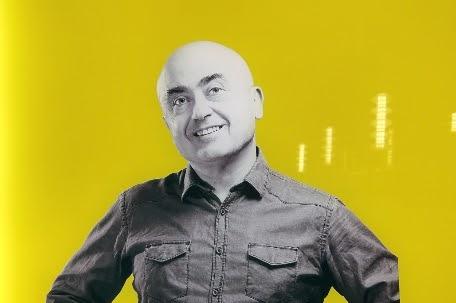 sfondo giallo, uomo in bianco e nero calvo con camicia, inquadratura solo Busto, comico Paolo Cevoli
