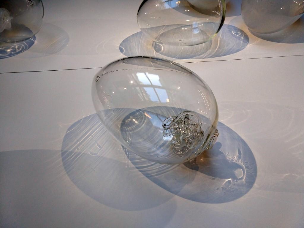 fotografia, interno, colori, uovo di vetro appoggiato su tavolo bianco, opera di Laura de Santillana
