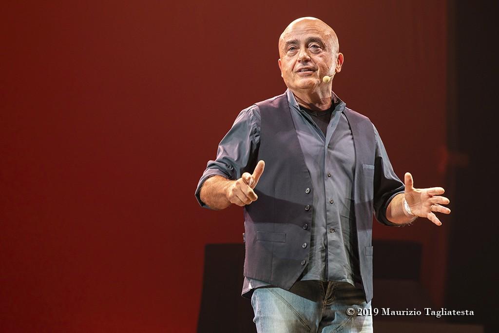 fotografia, colori, uomo calvo in jeans e camicia scura su palcoscenico, sfondo rosso,