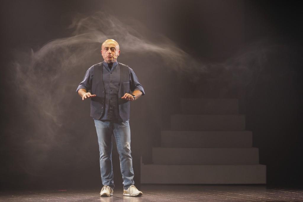 fotografia, colori, uomo calvo in jeans e camicia scura su palcoscenico, sfondo nero,