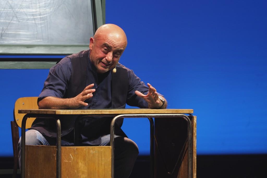 fotografia, colori, uomo calvo in jeans e camicia scura su palcoscenico seduto a un banco di scuola, sfondo blu