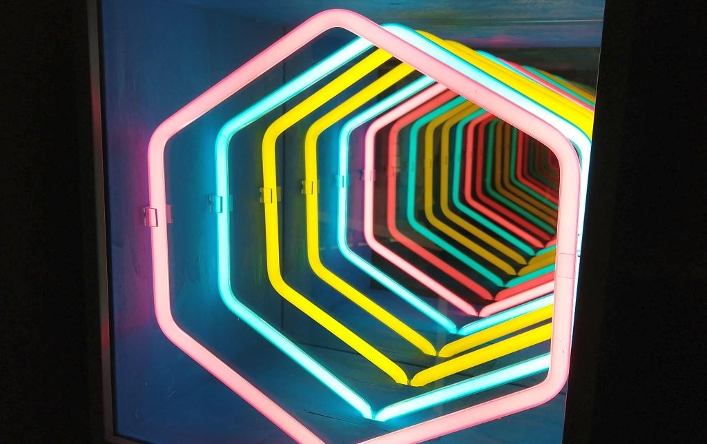 Fotografia colori, opera arte contemporanea Paolo Scirpa, scatola con tubi al neon rosa, giallo, blu e specchi