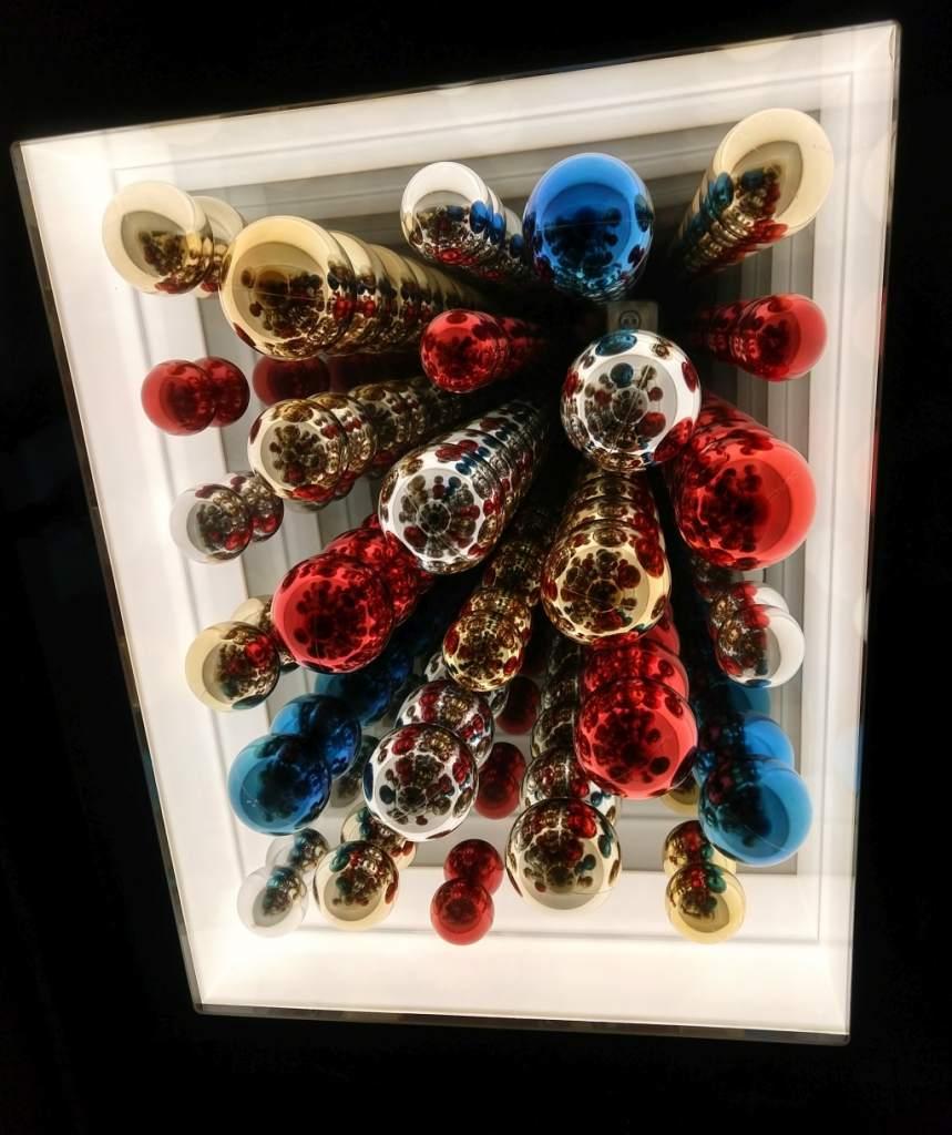 Fotografia colori, opera arte contemporanea Paolo Scirpa, scatola con palline di natale blu, oro, rosse, argento e specchi