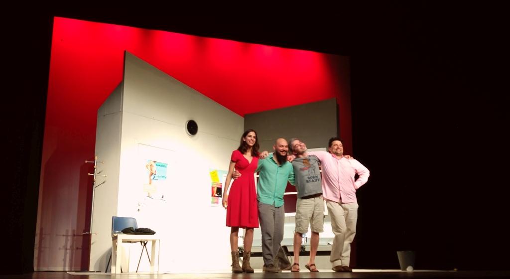 fotografia, colori, interno, 4 personaggi su palcoscenico, in linea si abbracciano e ricevono applausi del pubblico, da sinistra una ragazza e tre uomini