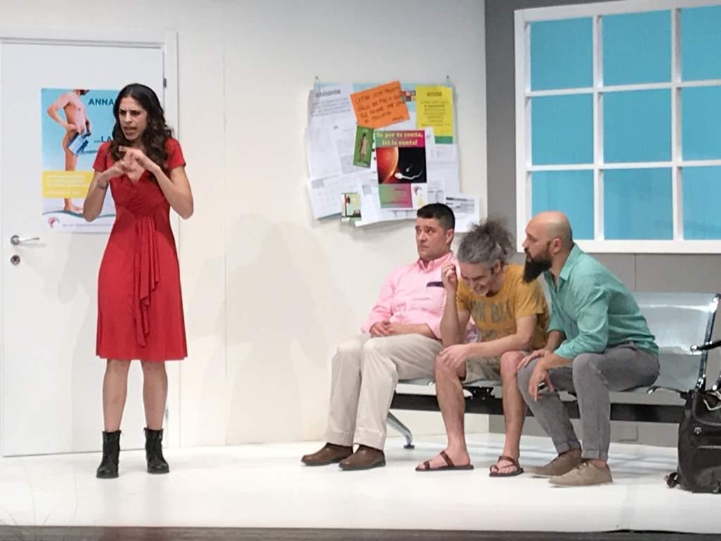 fotografia, colori, interno, 4 personaggi su palcoscenico, a sinistra una ragazza in piedi, a destra tre uomini seduti su poltrone sala d'aspetto