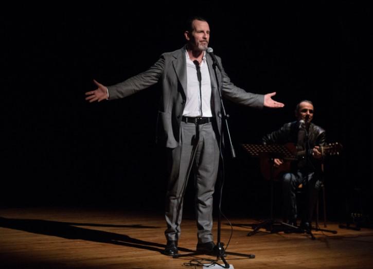 fotografia, colori, interno, palcoscenico, attore uomo in primo piani con abito grigio e braccia allargate, secondo piano chitarrista seduto, sfondo nero