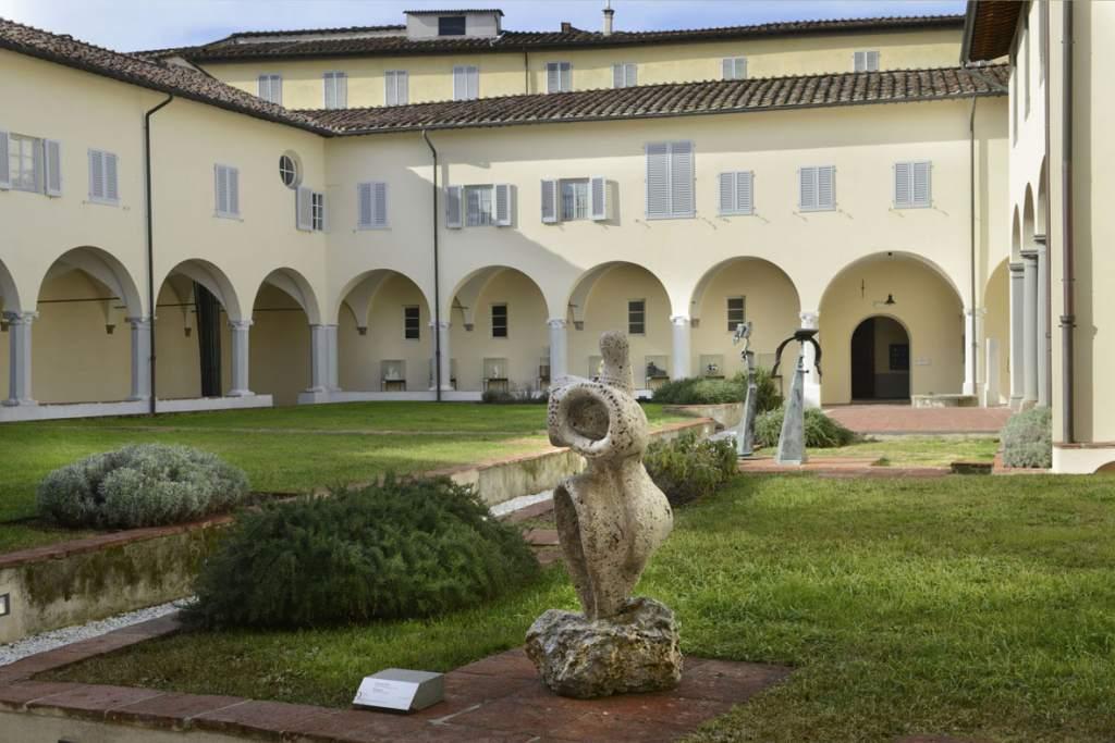 fotografia, colori, esterno, prato verde, edificio medievale chiaro, chiostro monastero, cielo azzurro, sede della Fondazione Ragghianti di Lucca