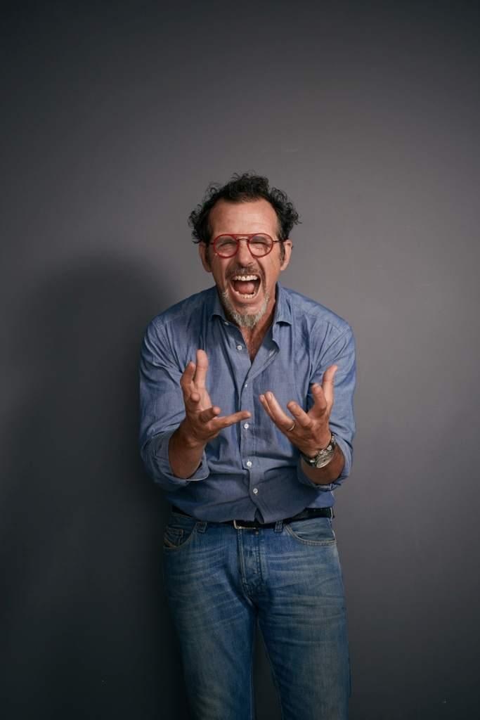 fotografia, colori, primo piano attore comico Germano Lanzoni, uomo mezz'età con pizzetto e occhiali tondi montatura rossa,camicia azzurra, urla e agita le mani verso spettatore
