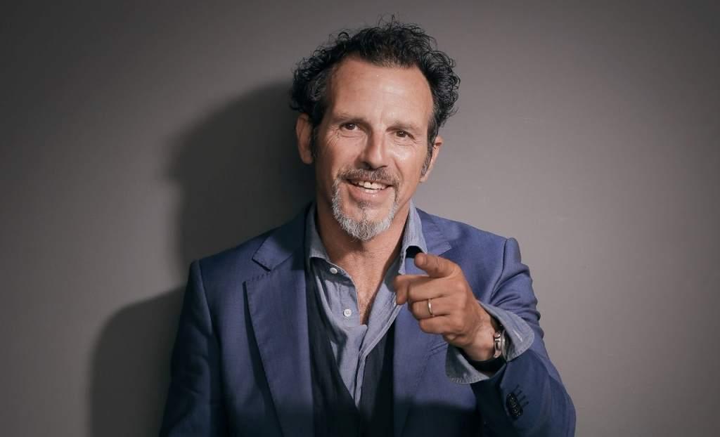 fotografia, colori, primo piano attore comico Germano Lanzoni, uomo mezz'età con pizzetto, elegante giacca blu, camicia azzurra, punta mano sinistra con indice verso spettatore