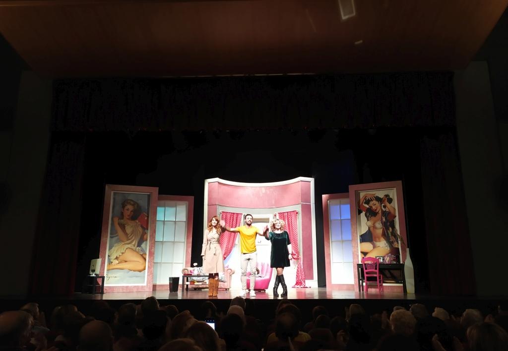 """fotografia, colori, interno, 3 attori su palcoscenico, 2 donne ai lati, uomo al centro, scenografia stanza pareti rosa, spettacolo """"L'uomo perfetto"""" in scena al Teatro Martinitt di Milano"""