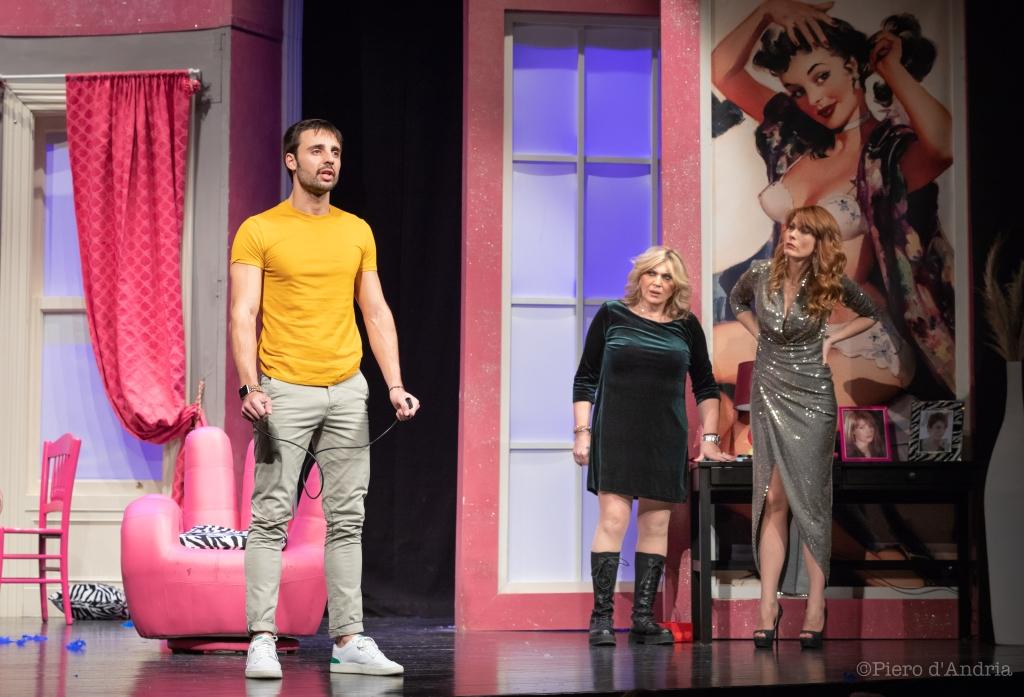 fotografia, colori, interno, 3 attori su palcoscenico, 2 donne ai lati, uomo al centro, scenografia stanza pareti rosa, spettacolo