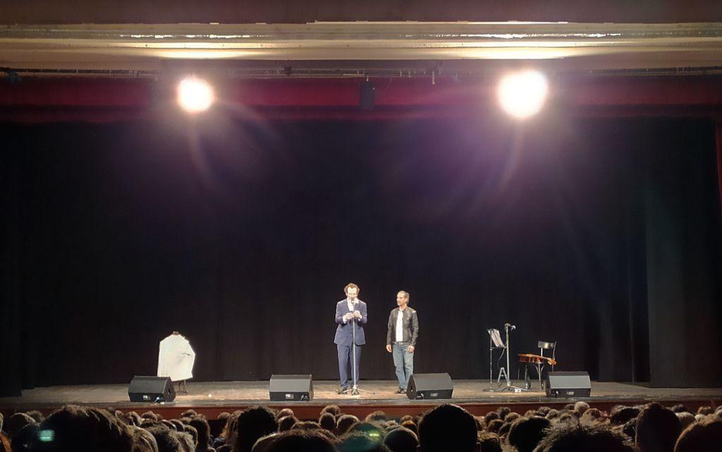fotografia, interno, colori, palcoscenico con 2 attori uomini, teste del pubblico in platea, quinte nere, sipario rosso