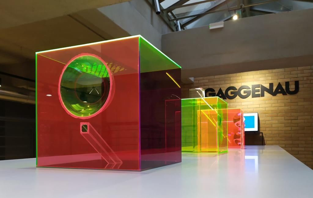 fotografia, colori, interno, 3 cubi di plexiglas colorato rosso, verde, giallo appoggiati su un grande tavolo bianco, sfondo mattoni e scritta gaggenau sul muro
