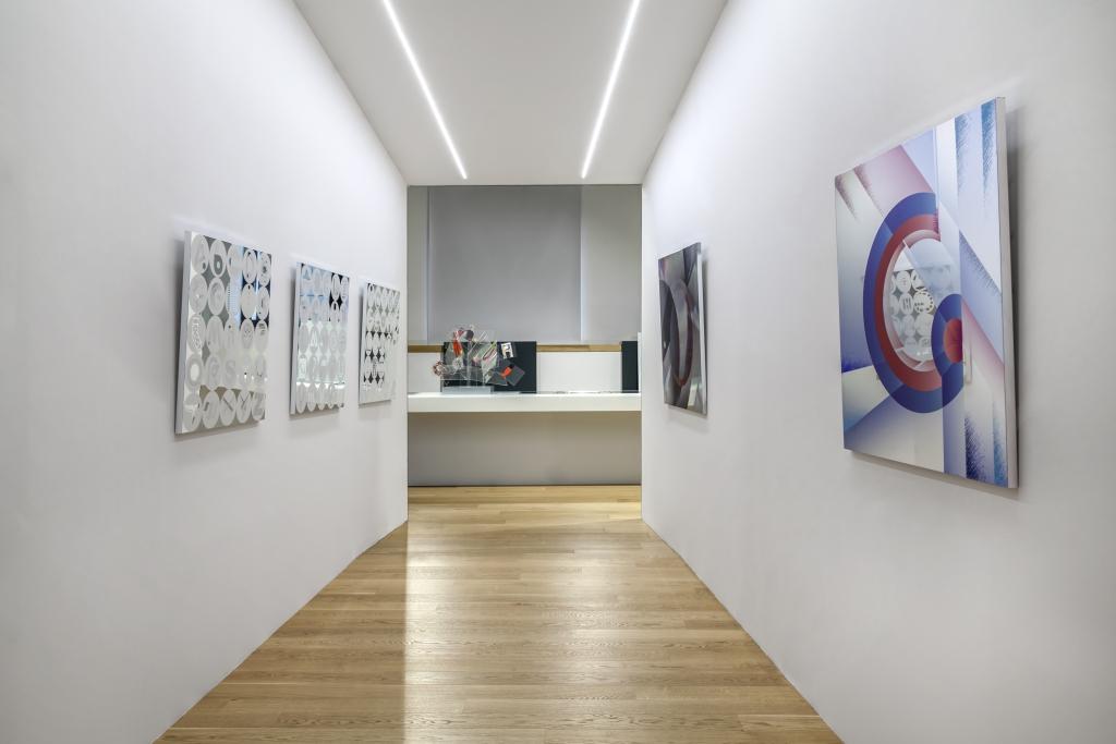 """fotografia, interno, colori, mostra """"Out of Words"""", corridoio con pareti bianche, pavimento parquet, 5 opere lastre di metallo con stampa appese alle pareti"""