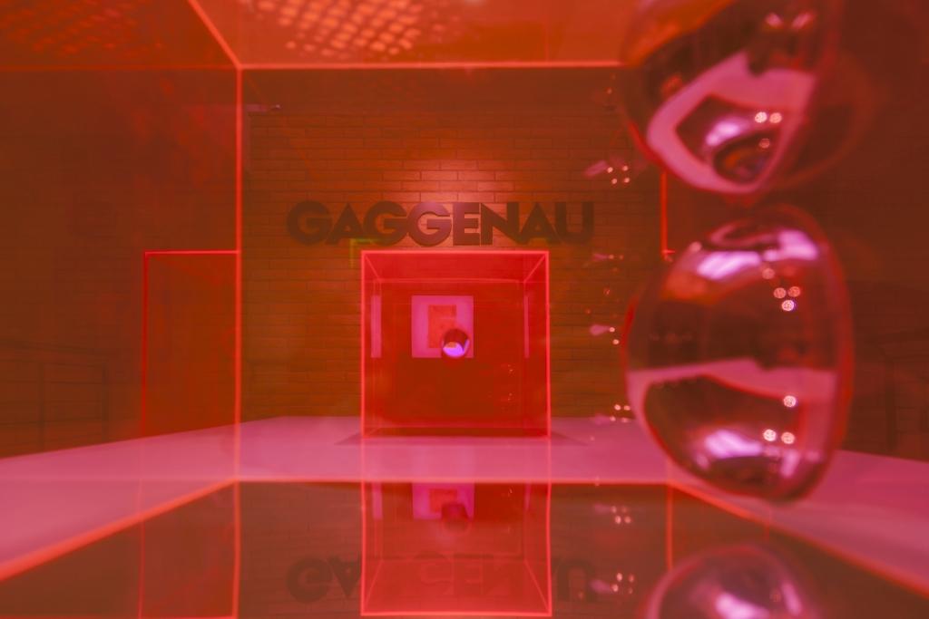 """fotografia, interno, colori, immagine della mostra """"Out of Words"""", plexiglas trasparente rosso che colora tutta foto, sfondo parete in mattoni"""