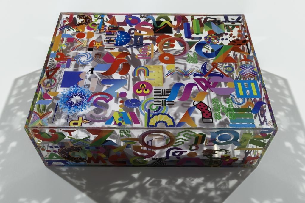fotografia, colori, interno, opera d'arte di Lorenzo Marini, parallelepipedo in plexiglas, icone e loghi colorati stampati, all'interno libro