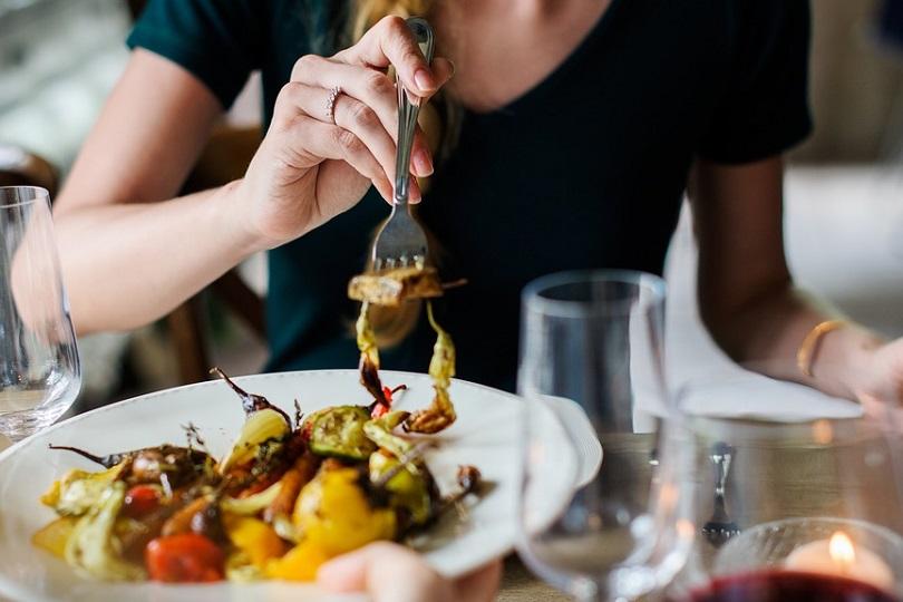donna seduta a tacola mentre sta inforchettando il cibo dal piatto