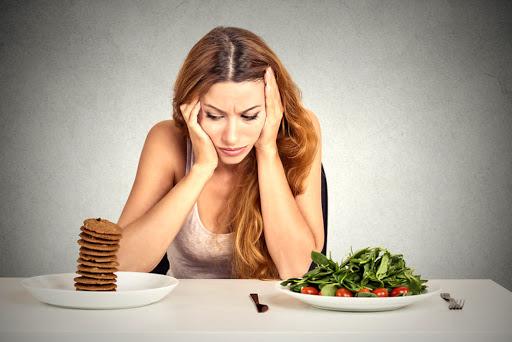 ragazza seduta al tavolo, sul tavolo ci sono due piatti, su uno le frittelle sull'altro insalata e pomodori