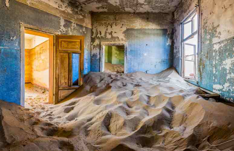 immagine di interno di una casa a Kolmanskop sommersa dalla sabbia