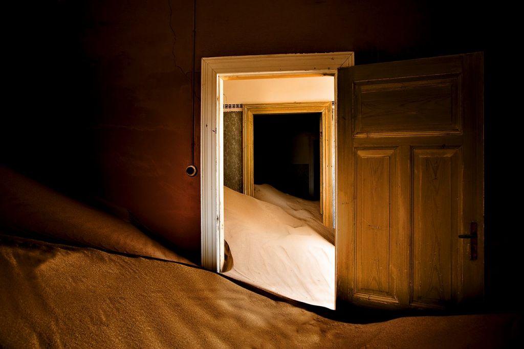 Interno di una casa a Kolmanskop in primo piano una porta sommersa di sabbia