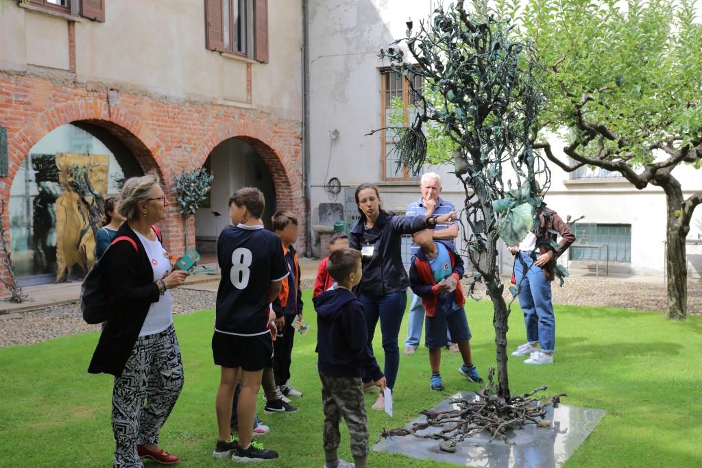 fotografia, colori, giardino con alberi e sculture bronzo di Alik Cavaliere, gruppo di visitatori con ragazzi