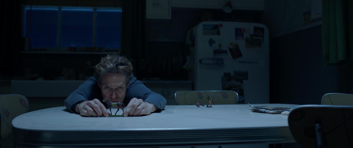 scena del film Siberia attore seduto a un tavolo con le braccia allungate verso la telecamera e un cavallo giocattolo in mano in una cucina buia