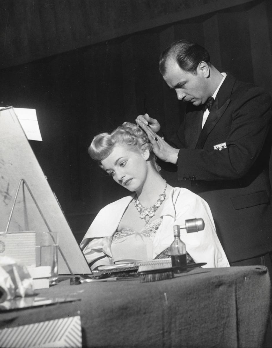 fotografai epoca, bianco e nero, giovane donna bionda seduta, uomo elegante in piedi la pettina