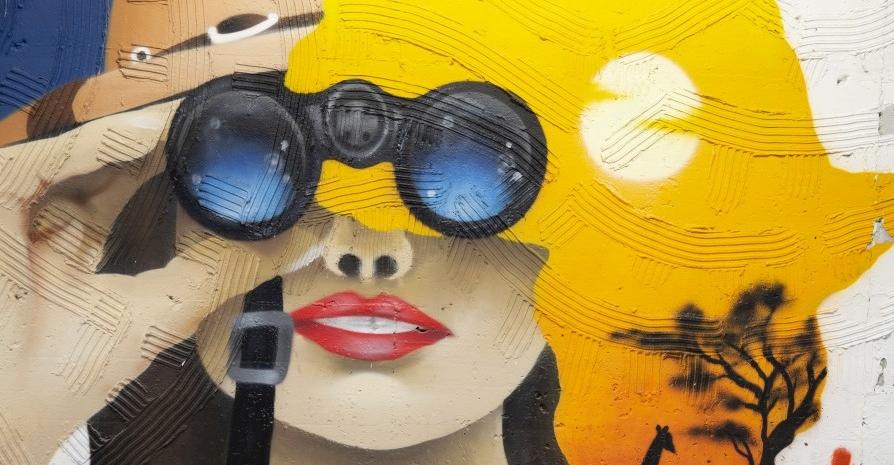 MuseoCity 2020, fotografia, colori, street art, primo piano volto donna che guarda con binocolo
