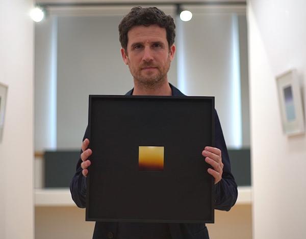 fotografia, colori, interno, artista Davide Tranchina regge sua opera, polaroid gialla con cornice nera
