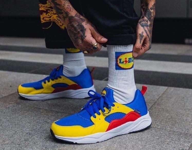 scarpe da ginnastica Lidl nei colori blu rosso e giallo con calzino bianxo e logo lidl