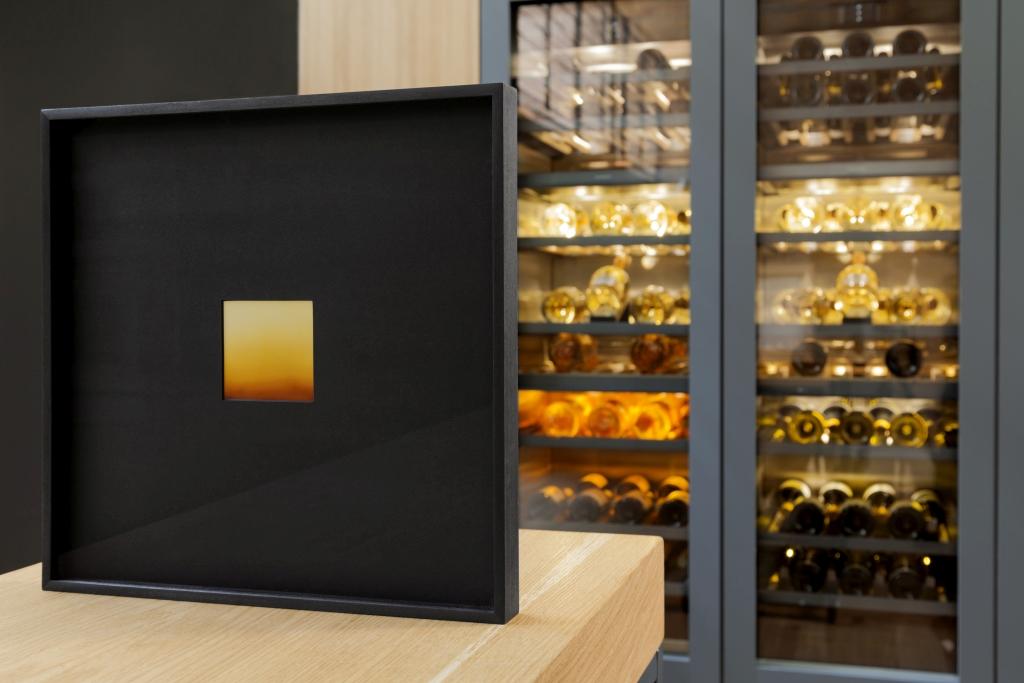 fotografia, colori, interno, Davide Tranchina mostra fotografica, foto di orizzonte giallo e nero, appoggiata su superficie in legno