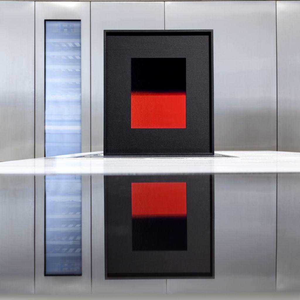 fotografia, colori, interno, Davide Tranchina mostra fotografica, foto di orizzonte rosso e nero, appoggiata su superficie a specchio