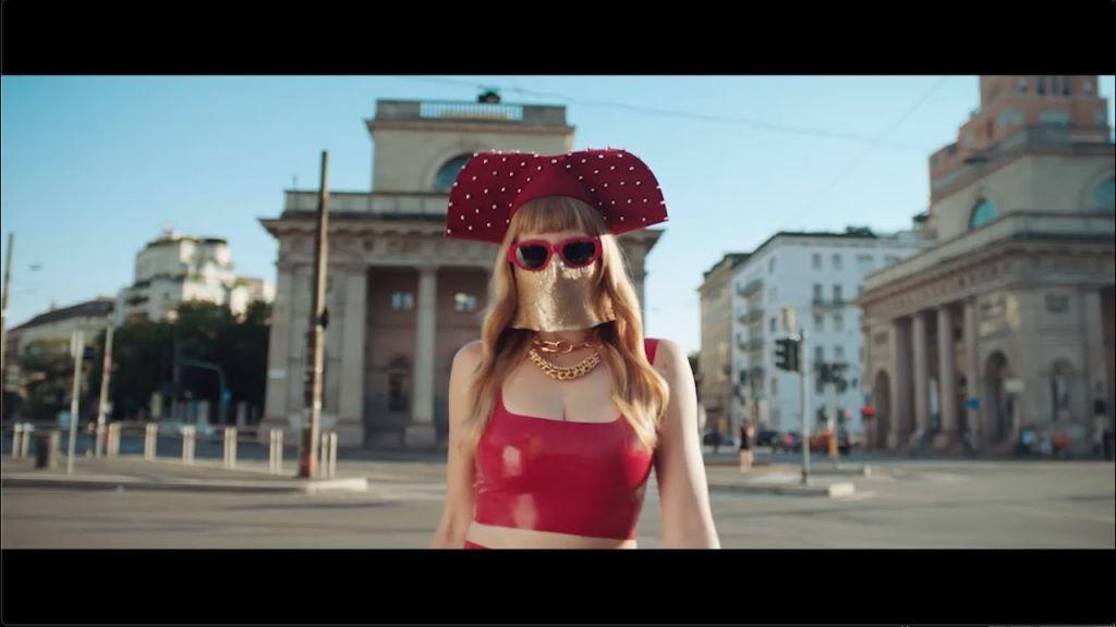 Sfondo Milano in primo piano ragazza vestita di sotto con cappello rosso e maschera davanti alla faccia Miss keta