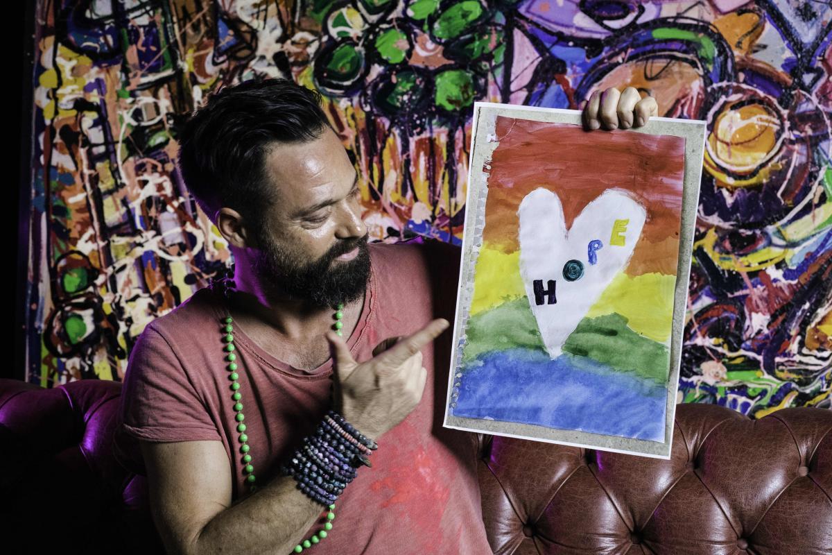 artista Sacha Jafri con in mano un disegno di un cuore con scritto al centro hope
