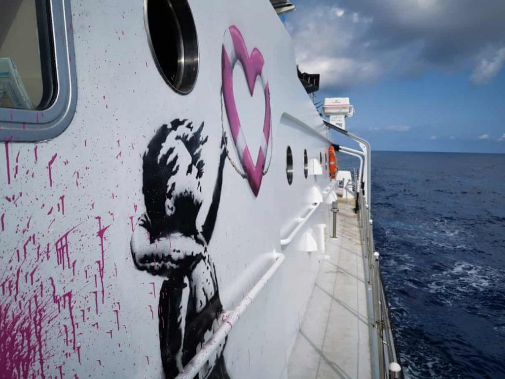 un dettaglio del lato della barca Louise Michel dove si vede il disegno di una bambina con un giubbotto di salvataggio che prende un salvagente