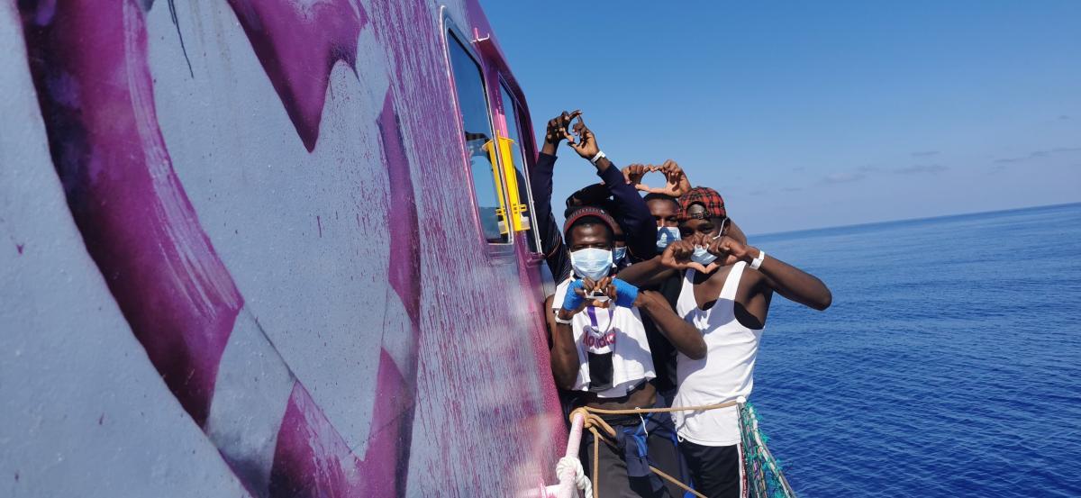 una foto di alcune persone sulla barca Louise-Michel che fanno con le mani il simbolo del cuore