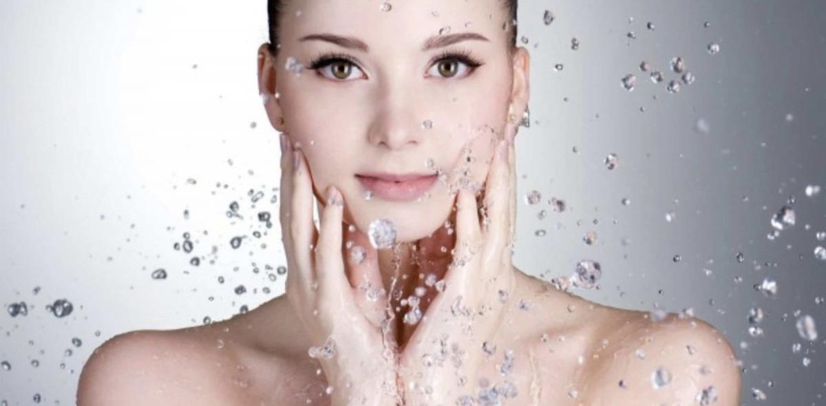 una donna in primo piano che si tocca il viso con le mani mentre le arrivano goccioline di acqua addosso