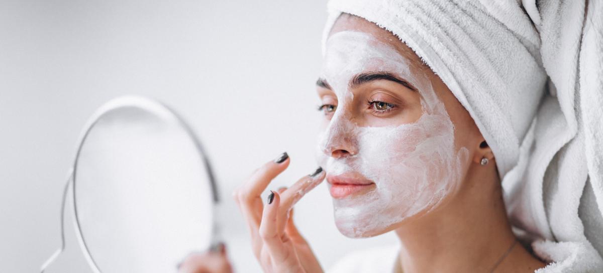in primo piano il viso di una donna con una maschera di bellezza mentre di guarda allo specchio