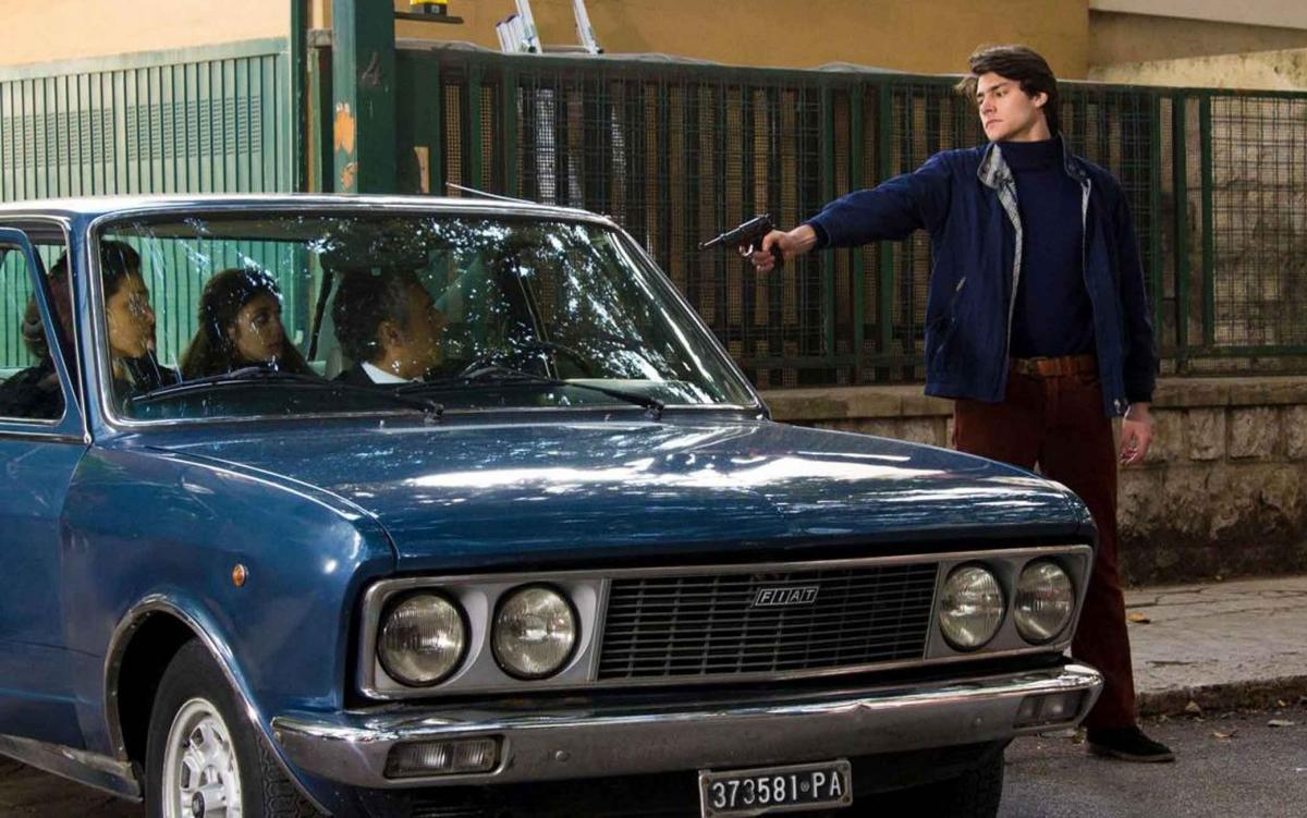 una scena tratta dal film Il delitto Mattarella un uomo in piedi punta una pistola verso il guidatore nella macchina blu