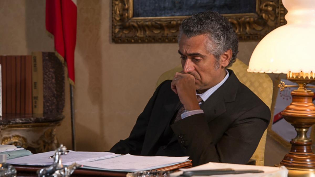 una scena del film Il delitto Mattarella una persona seduta alla scrivania mente pensa