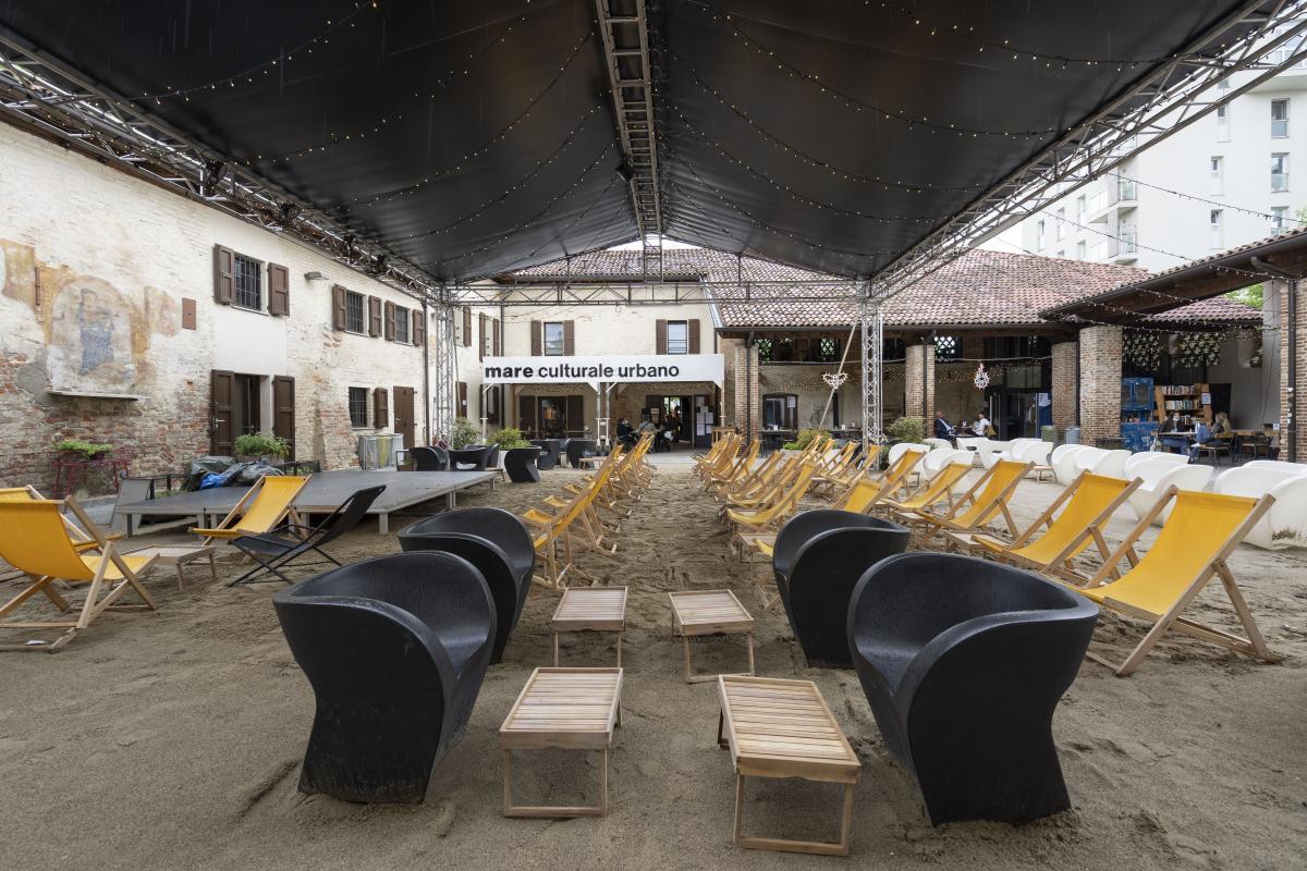 foto dell'interno dello spazio di mare culturale urbano con sedie e sdraio su sabbia